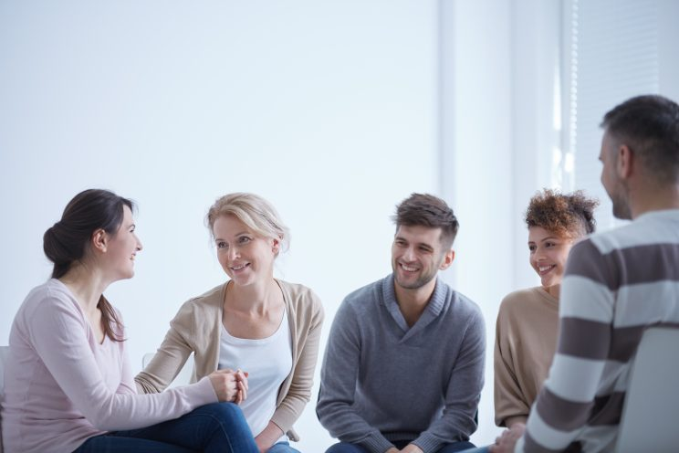 a group engage in a psychotherapy session in our toronto office