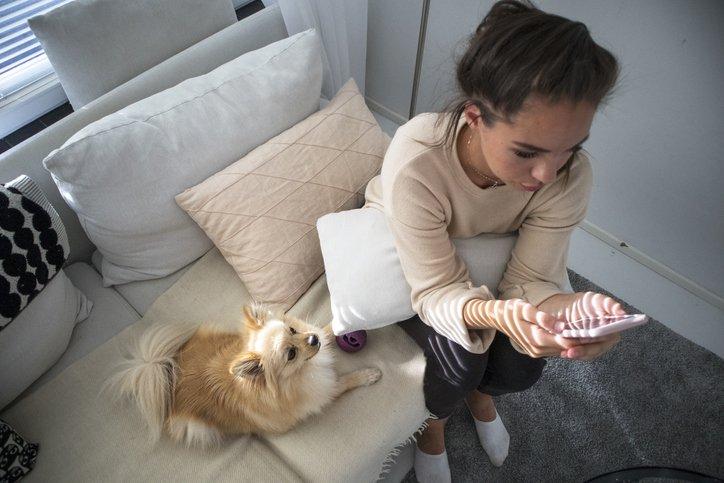 kobieta patrzy na aplikację randkową, czując niską samoocenę i odrzucenie społeczne