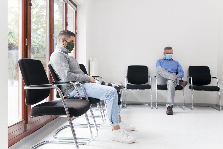 man sits in doctors office paying attention to how his feet feel on the ground